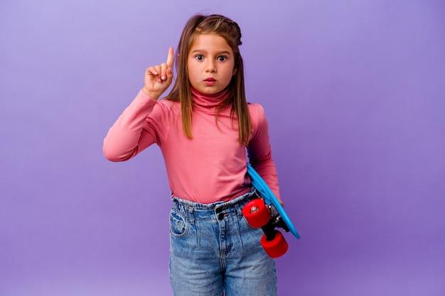 Petite fille caucasienne patineuse isolée sur fond bleu ayant une bonne idée, concept de créativité.