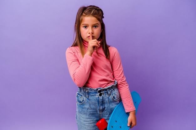 Petite fille caucasienne patineuse isolée sur fond bleu gardant un secret ou demandant le silence.