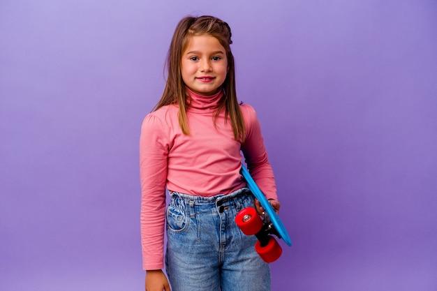 Petite fille caucasienne patineuse isolée sur fond bleu en riant et en s'amusant.