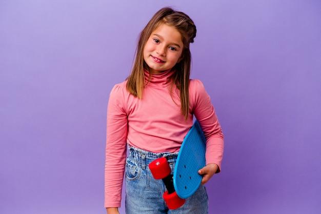 Petite fille caucasienne patineuse isolée sur mur bleu heureux, souriant et joyeux.