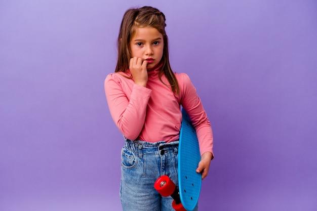 Petite fille caucasienne patineuse isolée sur les ongles mordants bleus, nerveuse et très anxieuse.