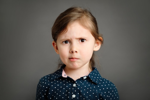 Petite fille caucasienne perplexe de 4 à 6 ans dans une robe bleue sur fond gris portrait en studio
