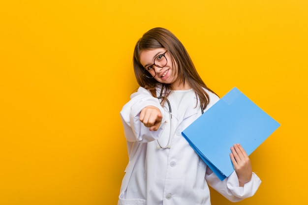Petite fille caucasienne portant un costume de médecin sourires joyeux pointant vers l'avant