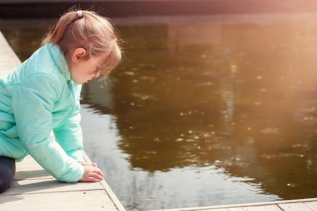 Petite fille caucasienne solitaire assise au bord de l'eau du lac et regardant l'eau. surface de l'eau du lac
