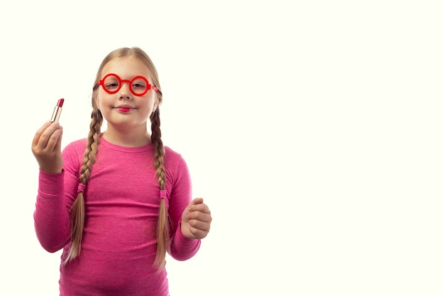 Une petite fille caucasienne sympathique peint ses lèvres avec du rouge à lèvres rouge sur fond blanc