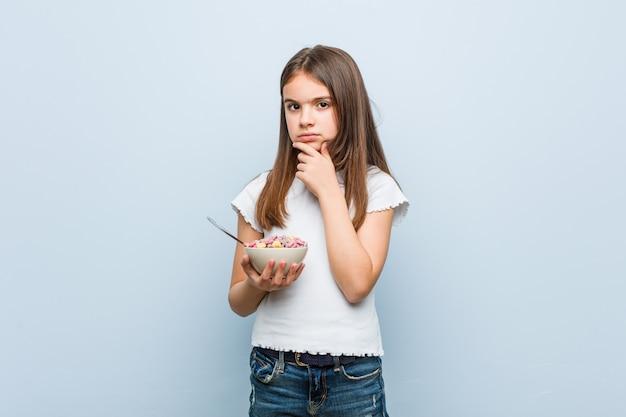 Petite fille caucasienne tenant un bol de céréales à la recherche de côté avec une expression douteuse et sceptique.