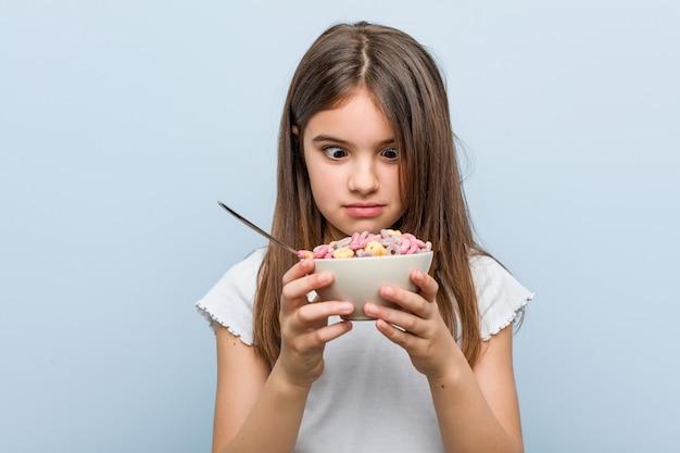 Petite fille caucasienne tenant un bol de céréales