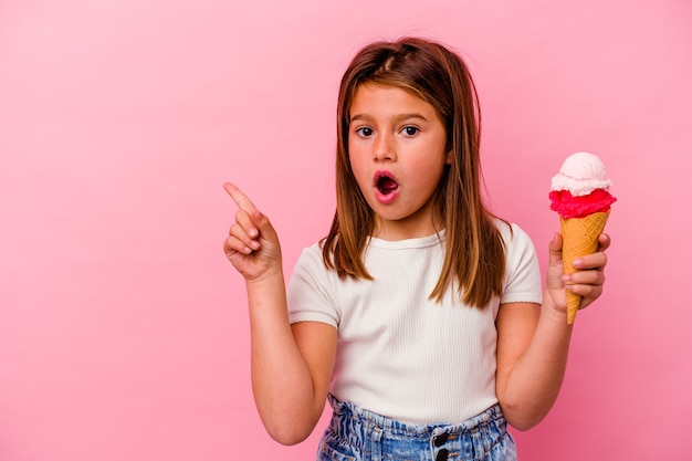 Petite fille caucasienne tenant la crème glacée isolée sur fond rose pointant vers le côté