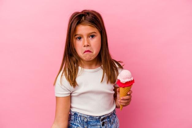 Petite fille caucasienne tenant une glace isolée sur fond rose hausse les épaules et ouvre les yeux confus.