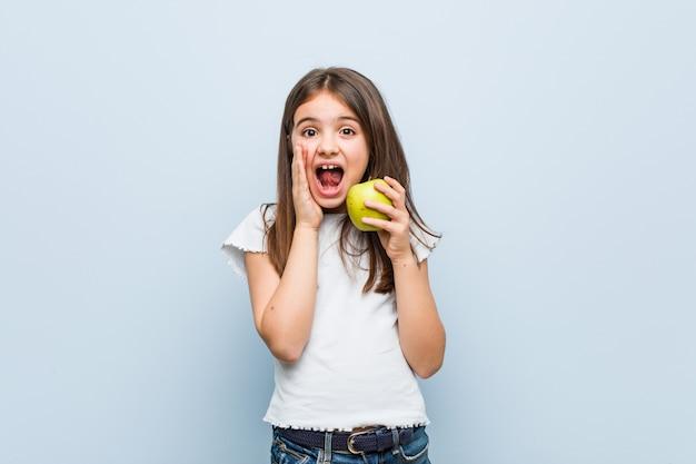 Petite fille caucasienne tenant une pomme verte criant excitée à l'avant.