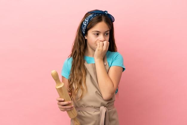 Petite fille caucasienne tenant un rouleau à pâtisserie isolé sur fond rose ayant des doutes