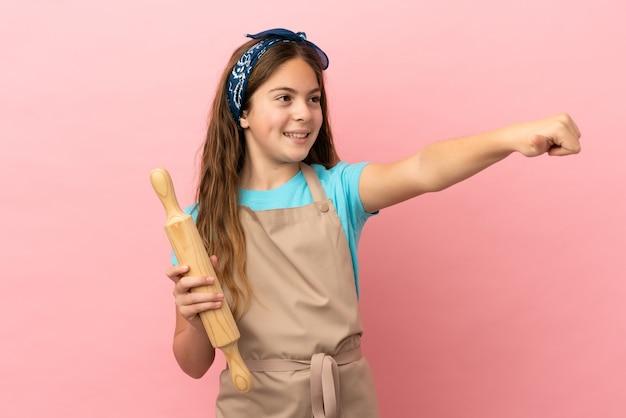 Petite fille caucasienne tenant un rouleau à pâtisserie isolé sur fond rose donnant un geste du pouce vers le haut
