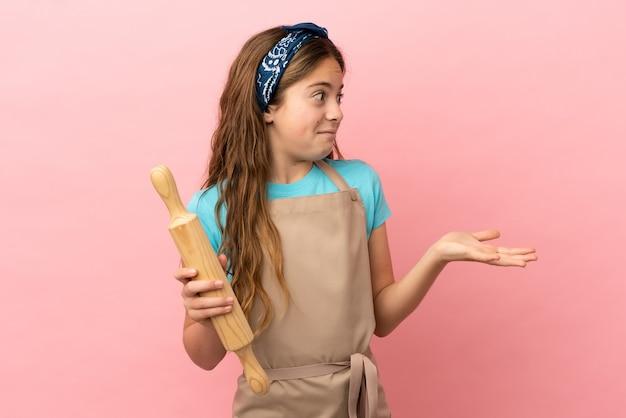 Petite fille caucasienne tenant un rouleau à pâtisserie isolé sur fond rose avec une expression surprise tout en regardant de côté