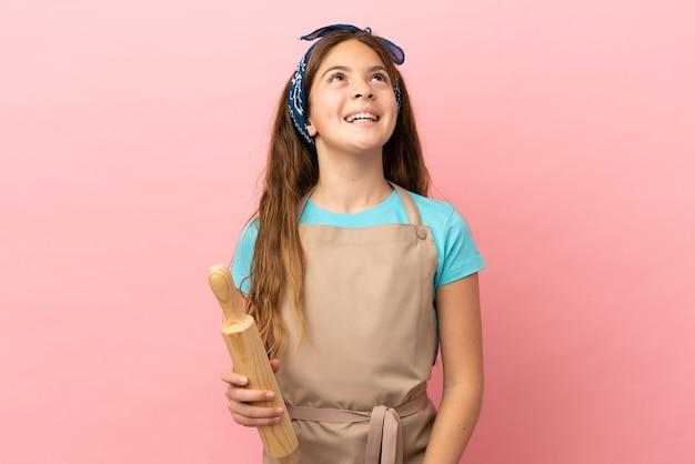Petite fille caucasienne tenant un rouleau à pâtisserie isolé sur fond rose en riant