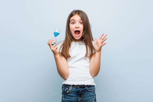 Petite fille caucasienne tenant un sablier célébrant une victoire ou un succès