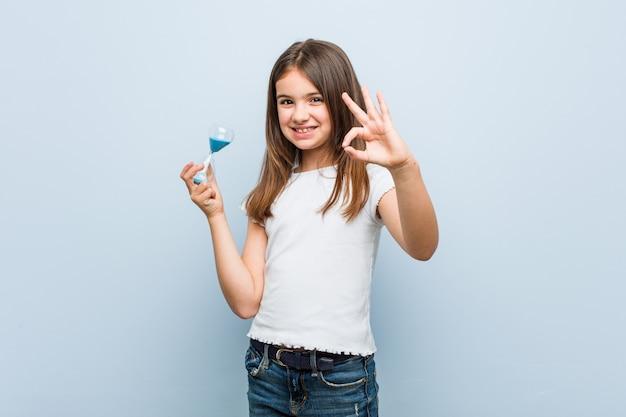 Petite fille caucasienne tenant un sablier gai et confiant montrant le geste ok.