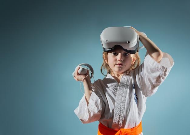 Petite fille caucasienne en uniforme de karaté jouant à des jeux vidéo avec casque vr
