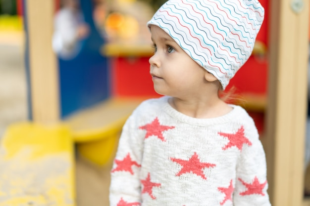 Petite fille caucasienne vêtue d'un chapeau et d'un pull