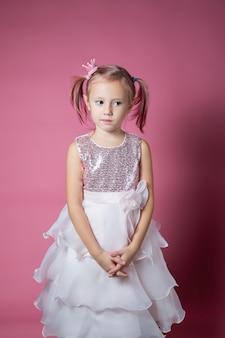 Petite fille caucasienne vêtue d'une robe de fête avec des paillettes posant comme une princesse sur fond rose en regardant la caméra