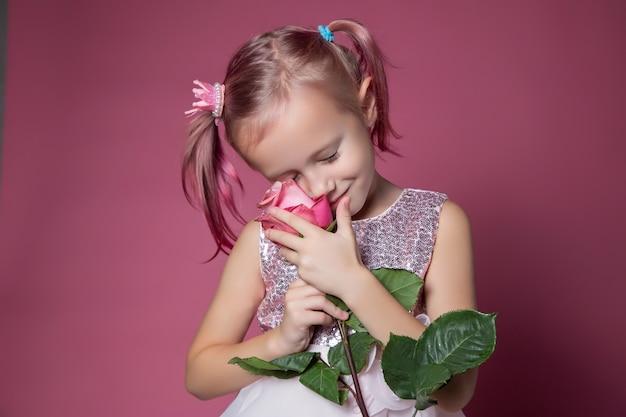 Petite fille caucasienne vêtue d'une robe de fête avec des paillettes posant avec une fleur rose sur fond rose en regardant la caméra