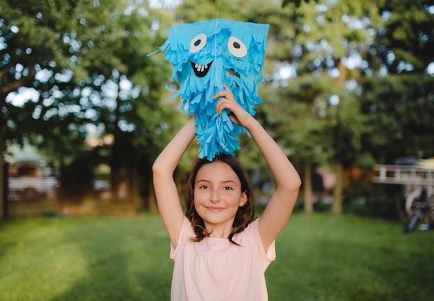 Petite fille avec cerf-volant debout à l'extérieur dans le jardin en été, un concept de célébration d'anniversaire.