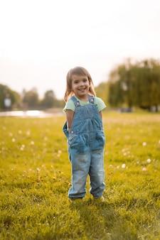Petite fille sur un champ de pissenlit, au coucher du soleil, enfant heureux émotionnel.
