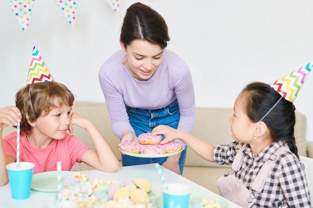 Petite fille en chapeau d'anniversaire en tenant le beignet de la plaque tenue par la mère tout en profitant d'une fête à la maison avec des amis par table servie