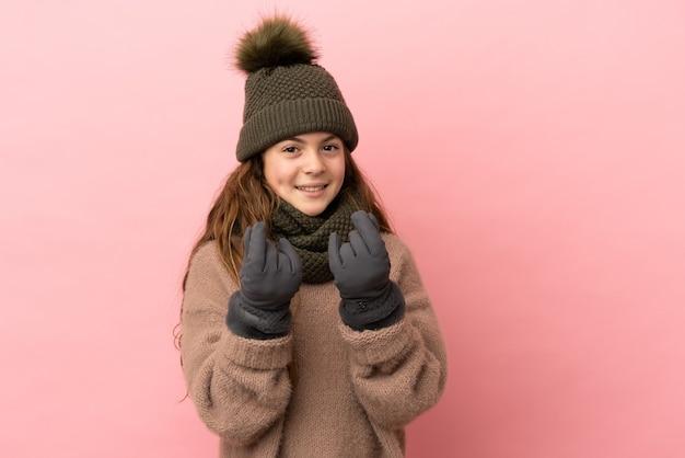 Petite fille avec un chapeau d'hiver isolé sur fond rose faisant un geste d'argent