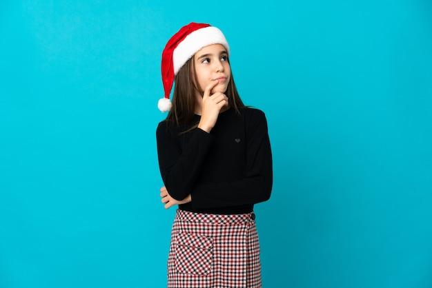 Petite fille avec chapeau de noël isolé sur fond bleu ayant des doutes en levant les yeux