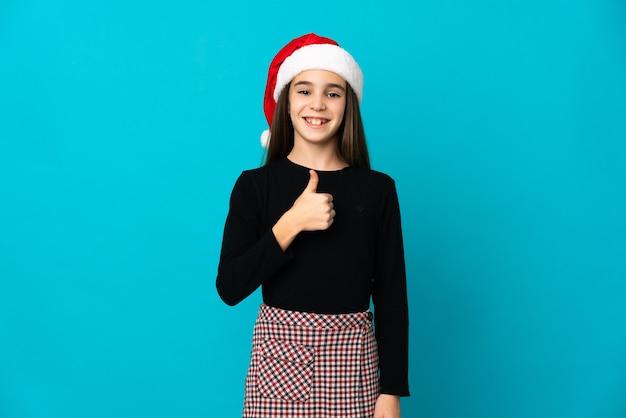 Petite fille avec un chapeau de noël isolé sur fond bleu donnant un geste de pouce en l'air