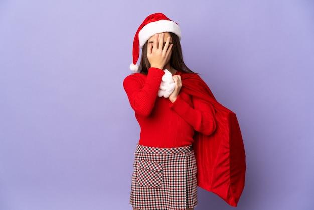 Petite fille avec chapeau et sac de noël isolé avec une expression fatiguée et malade