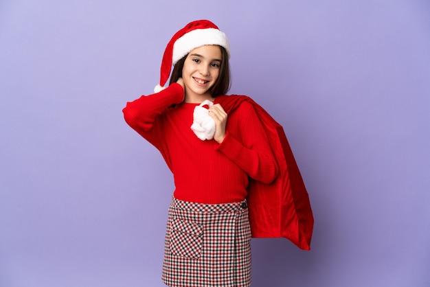 Petite fille avec chapeau et sac de noël isolé sur fond violet en riant