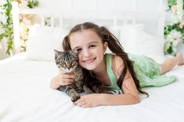 Petite fille avec un chat est allongée sur le lit