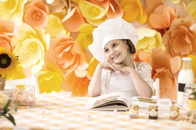 Petite fille avec le chef de livre préparant le petit déjeuner