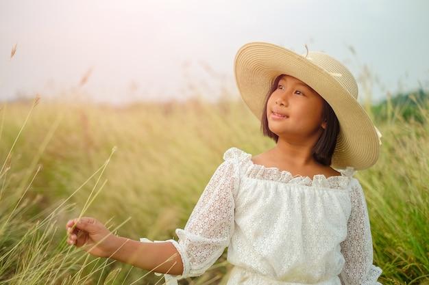 Petite fille en chemise de dentelle blanche porter chapeau de paille se sent détendu dans la belle prairie.