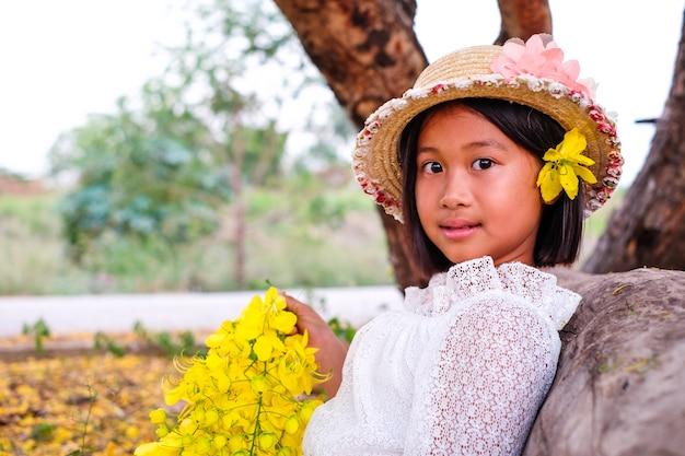 Une petite fille en chemise de dentelle blanche porter un chapeau de paille