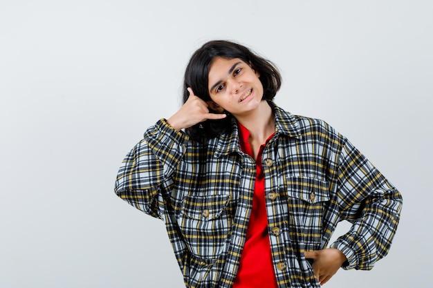 Petite fille en chemise, veste montrant le geste d'appel téléphonique, vue de face.