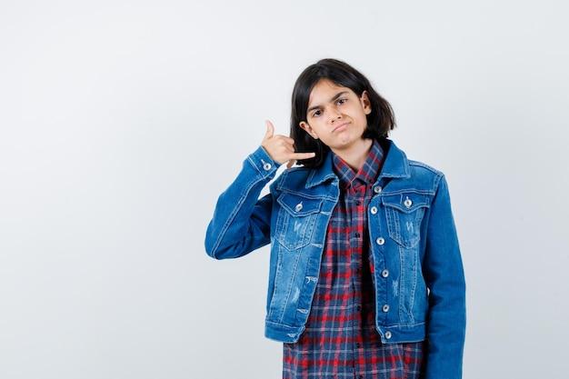 Petite fille en chemise, veste montrant le geste du téléphone et l'air confiant, vue de face.