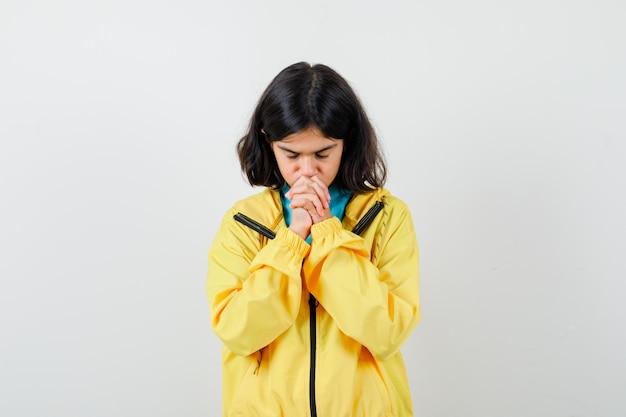 Petite fille en chemise, veste montrant les mains jointes dans un geste suppliant et l'air plein d'espoir, vue de face.