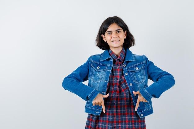 Petite fille en chemise, veste pointant vers le bas et l'air confiant, vue de face.