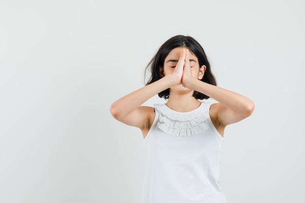 Petite fille en chemisier blanc, main dans la main en signe de prière et à la vue calme, de face.
