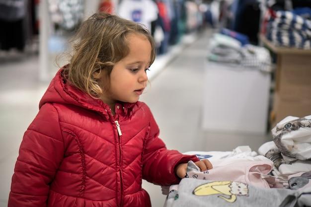 Petite fille cherche dans le magasin pour les ventes