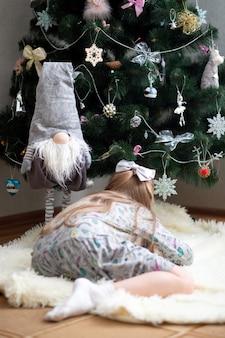 Une petite fille cherche quelque chose sous le sapin de noël à côté d'une naine grise