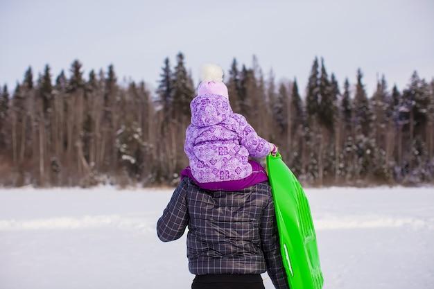Petite fille à cheval sur le jeune père à l'extérieur en froide journée d'hiver