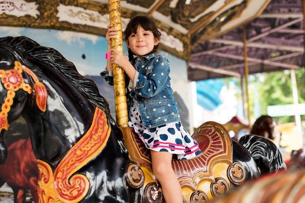 Petite fille sur un cheval de manège