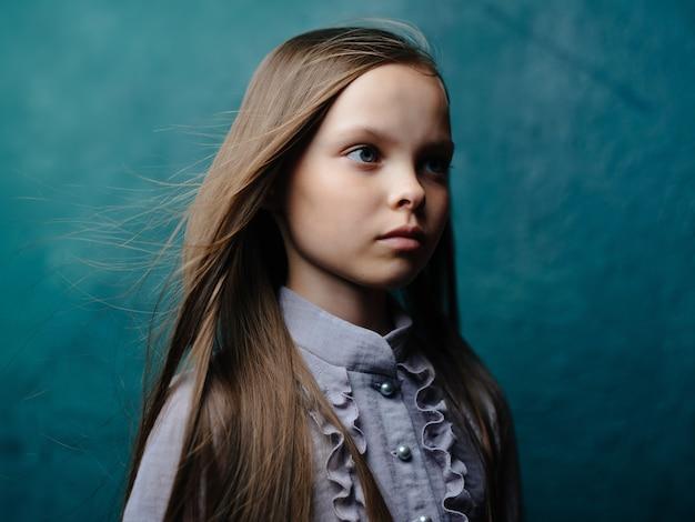 Petite fille cheveux longs en robe posant fond isolé. photo de haute qualité