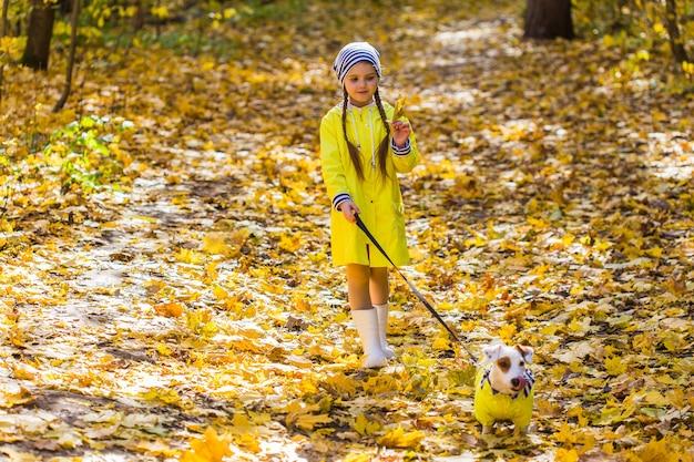 Petite fille avec un chien jack russell terrier. concept d'enfant, d'enfance, d'amitié et d'animal de compagnie. petit chien