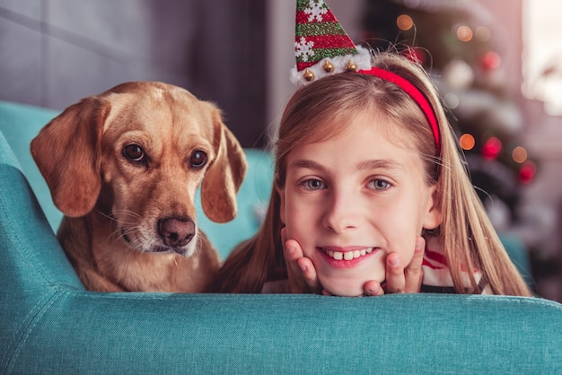 Petite fille avec un chien jaune posant sur un canapé
