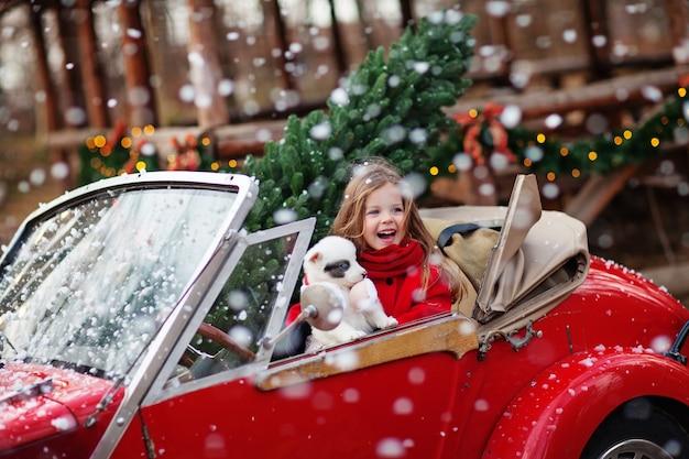Petite fille avec un chiot husky rit sous la neige dans une voiture rouge