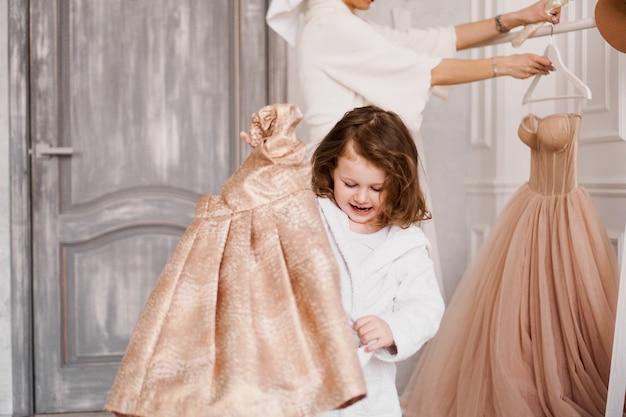La petite fille a choisi une robe beige dans l'armoire et va la porter. enfant heureux. maman en arrière-plan